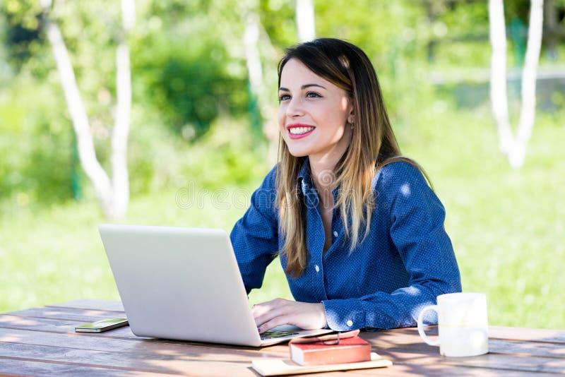 Uma mulher feliz bonita que usa o portátil fora fotos de stock royalty free