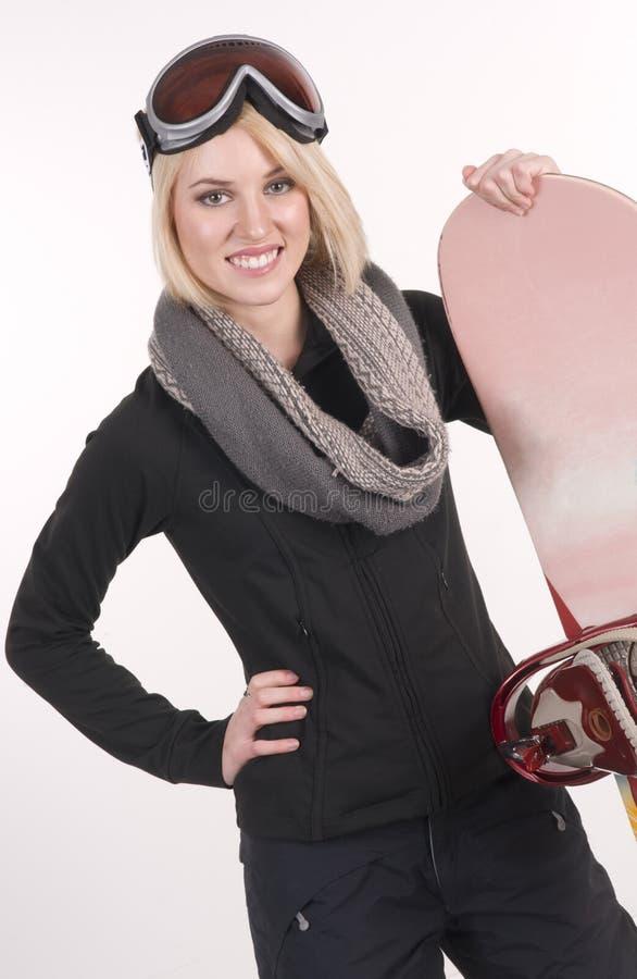 A mulher feliz dos esportes está na engrenagem completa com seu Snowboard foto de stock