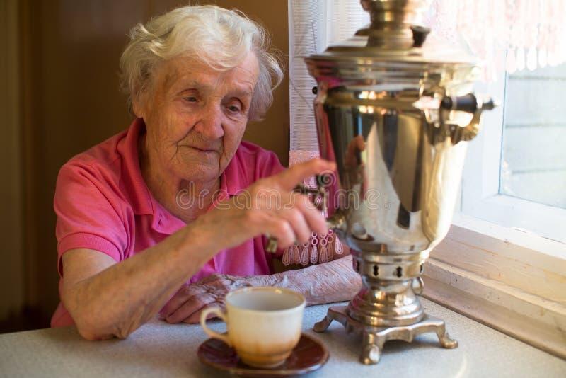 Uma mulher feliz idosa bebe o chá de um samovar do russo imagem de stock