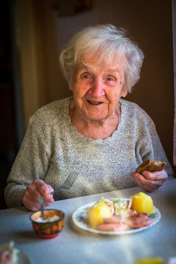 Uma mulher feliz idosa que come o almoço que senta-se na tabela foto de stock