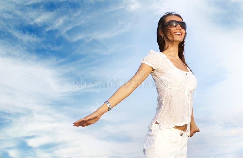 Uma mulher feliz nos vidros e em um vestido branco fotografia de stock royalty free