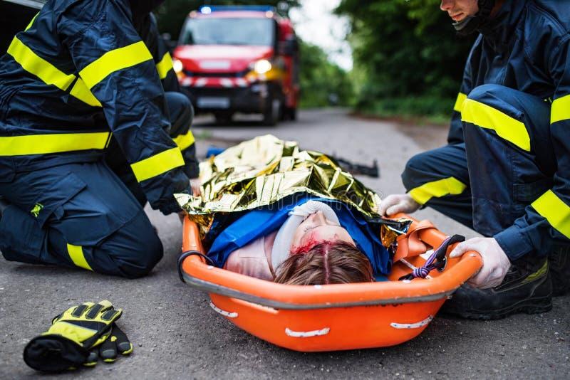 Uma mulher ferida em uma maca plástica após um acidente de trânsito, coberto pela cobertura térmica fotografia de stock