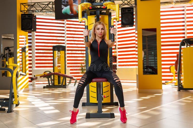 Uma mulher forte que faz um exercício que mistura e que levanta suas mãos no simulador no gym fotografia de stock royalty free