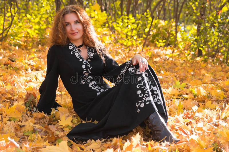 Uma mulher ginger-haired bonita na floresta da queda fotografia de stock