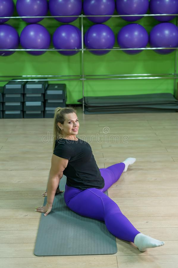 Uma mulher gorda está engajada na academia Uma garota com muito excesso de peso tentando perder peso com a ajuda de foto de stock
