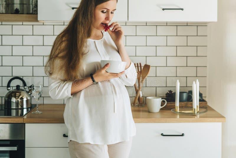 Uma mulher gravida atrativa nova com o cabelo longo, vestindo na camisa branca está estando na cozinha, inclinando-se na tabela fotos de stock
