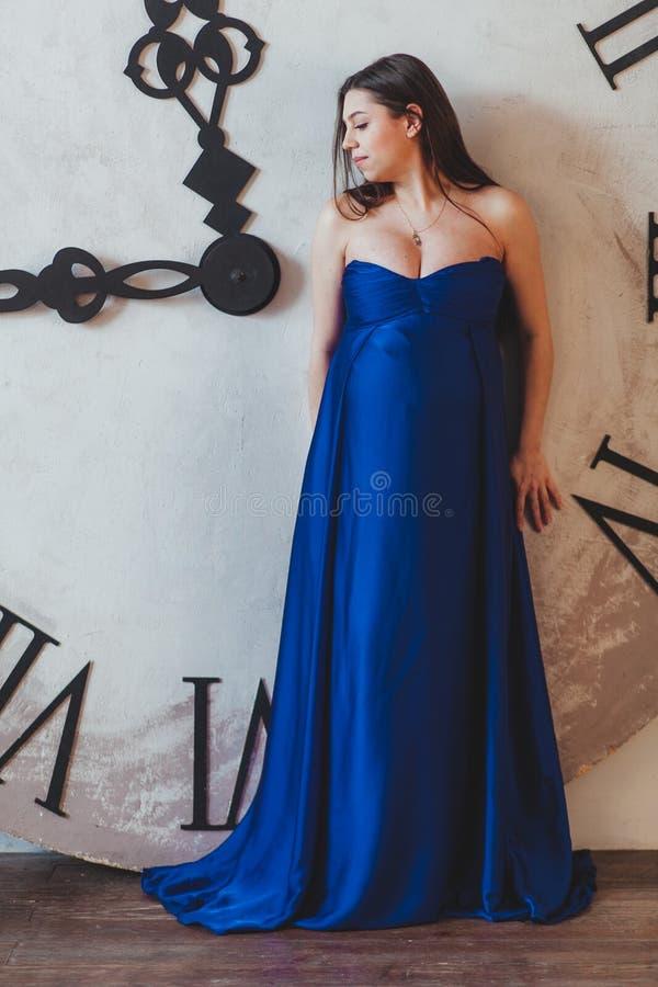 Uma mulher gravida em um vestido longo azul bonito que está na frente do pulso de disparo enorme fotos de stock royalty free