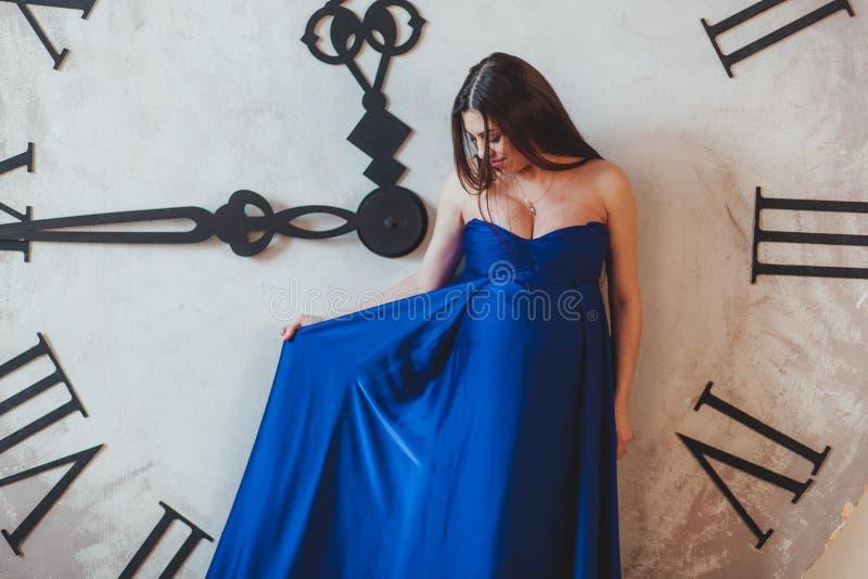 Uma mulher gravida em um vestido longo azul bonito que está na frente do pulso de disparo enorme fotos de stock