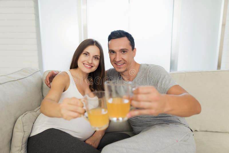 Uma mulher gravida encontra-se em um sofá leve Um homem está sentando-se ao lado dela Estão guardando os copos de vidro com suco imagem de stock