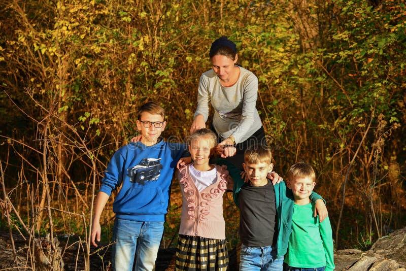 Uma mulher gravida está em uma floresta em uma árvore, e quatro crianças estão no parque ao lado de sua mãe Mãe de muitas criança fotos de stock