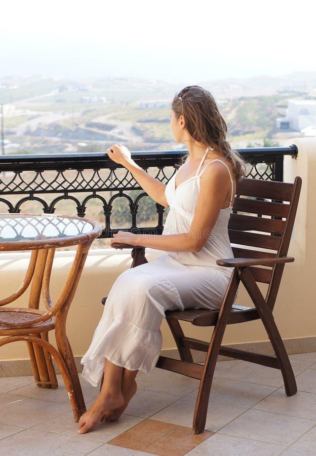 Uma mulher gravida nova em um vestido branco que senta-se em uma cadeira imagens de stock royalty free