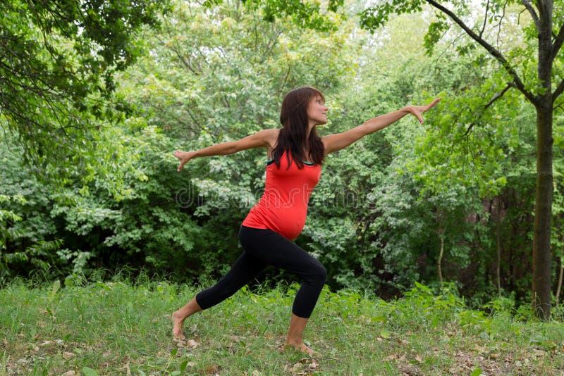 Uma mulher gravida que faz a ioga imagens de stock royalty free