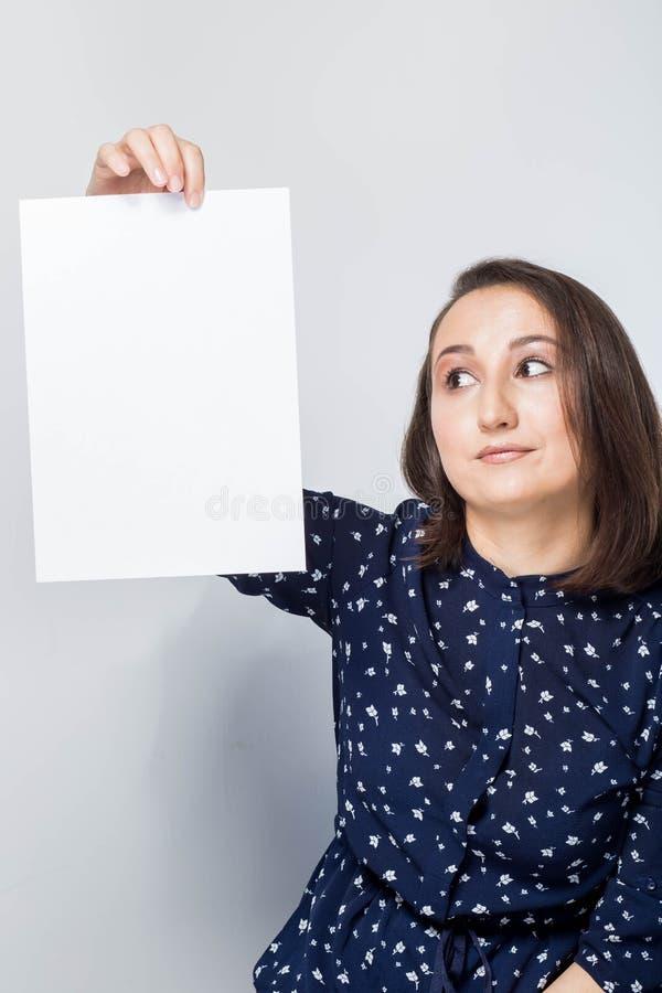 Uma mulher guarda uma folha de papel branca, um espaço da cópia para anunciar e olhares nele foto de stock