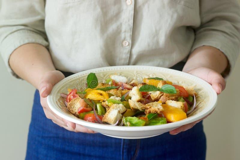 Uma mulher guarda uma placa com uma salada do panzanella em suas mãos Estilo rústico foto de stock royalty free