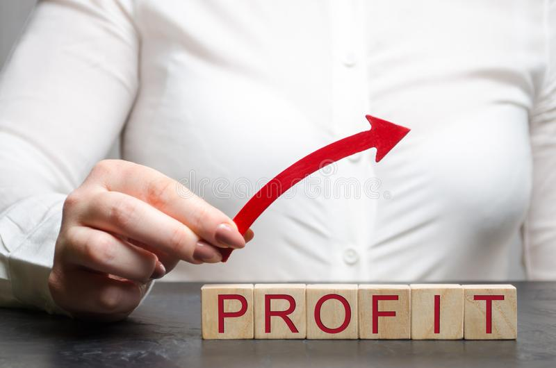 Uma mulher guarda uma seta ascendente acima dos blocos de madeira com o lucro da palavra O conceito de um negócio bem sucedido Cr foto de stock