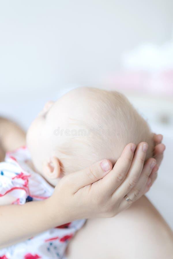 Uma mulher guarda seu bebê em casa fotografia de stock