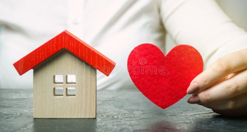 Uma mulher guarda um coração vermelho perto da casa de madeira Serviços do agente de seguros Conceito do seguro patrimonial Prote fotografia de stock