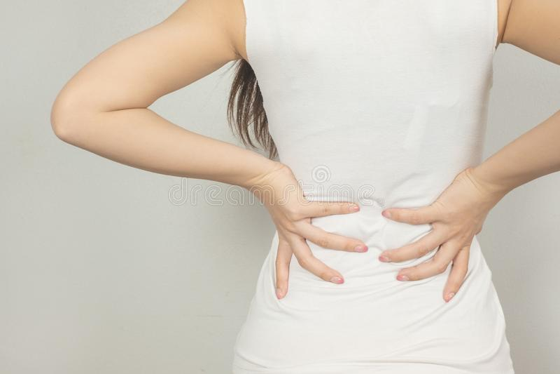 Uma mulher guardou sua mão atrás dele com dor nas costas Conceito dos cuidados m?dicos imagens de stock