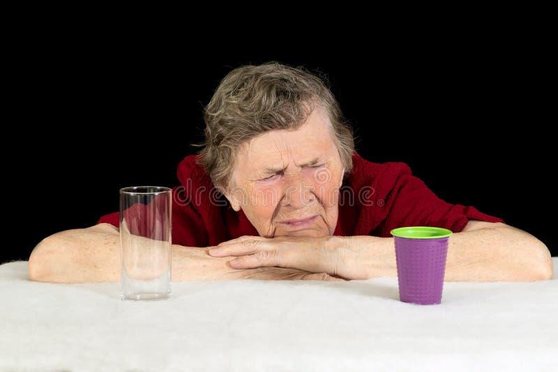Uma mulher idosa com cabelo e os enrugamentos cinzentos em seus olhares da cara no copo plástico descartável com aversão e despre imagem de stock