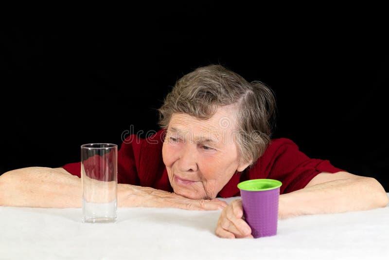 Uma mulher idosa com olhares cinzentos do cabelo nos produtos vidreiros com aprovação e um sorriso, empurrando o copo plástico af fotografia de stock