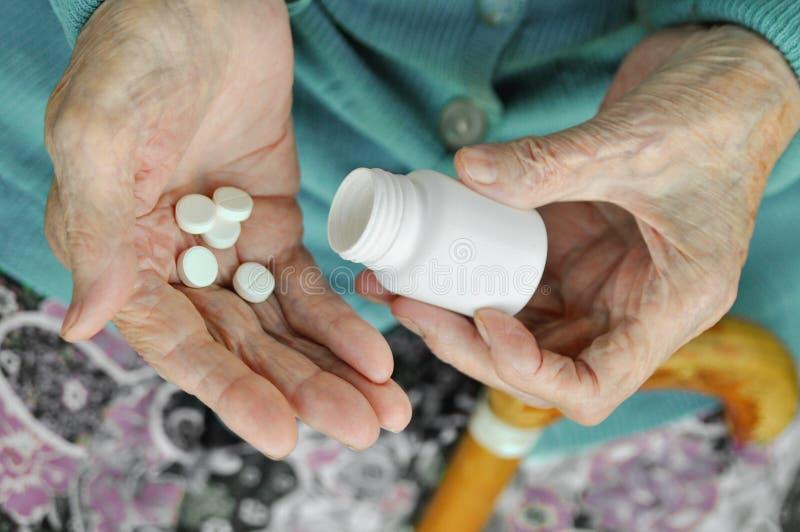 Uma mulher idosa com um bastão que guarda um comprimido e um recipiente na rua saúde Modelo Fim acima imagem de stock royalty free