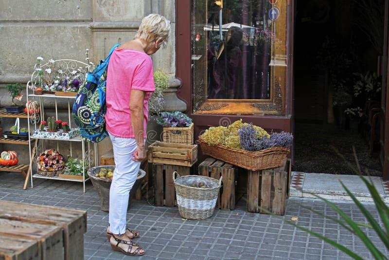Uma mulher idosa considera as flores exibidas na rua perto do florista em Barcelona imagens de stock royalty free