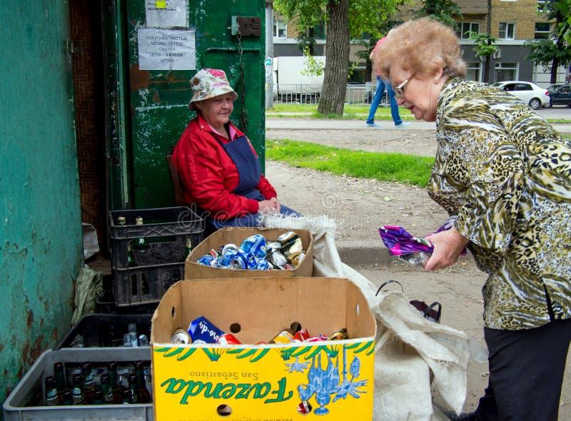 Uma mulher idosa dá materiais recicláveis em um ponto da recepção, a cidade de Voronezh imagens de stock