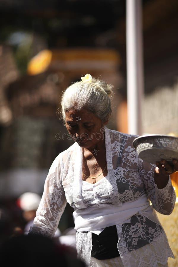 Uma mulher idosa do Balinese na roupa tradicional na cerimônia do templo hindu, ilha de Bali, Indonésia imagens de stock