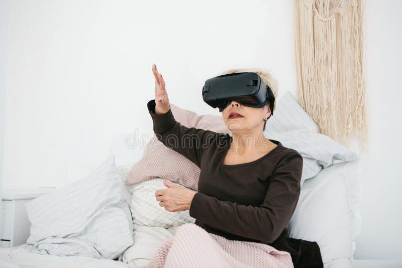 Uma mulher idosa em vidros da realidade virtual Uma pessoa idosa que usa a tecnologia moderna foto de stock royalty free