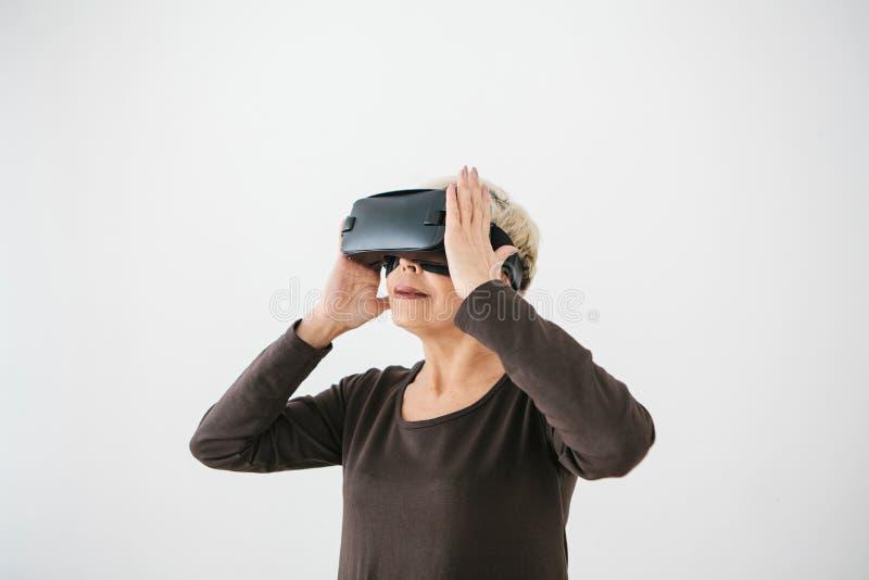 Uma mulher idosa em vidros da realidade virtual Uma pessoa idosa que usa a tecnologia moderna fotografia de stock