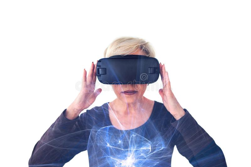 Uma mulher idosa em vidros da realidade virtual Uma pessoa idosa que usa a tecnologia moderna fotografia de stock royalty free