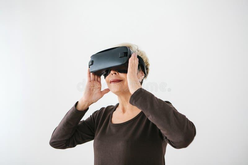 Uma mulher idosa em vidros da realidade virtual Uma pessoa idosa que usa a tecnologia moderna imagens de stock royalty free