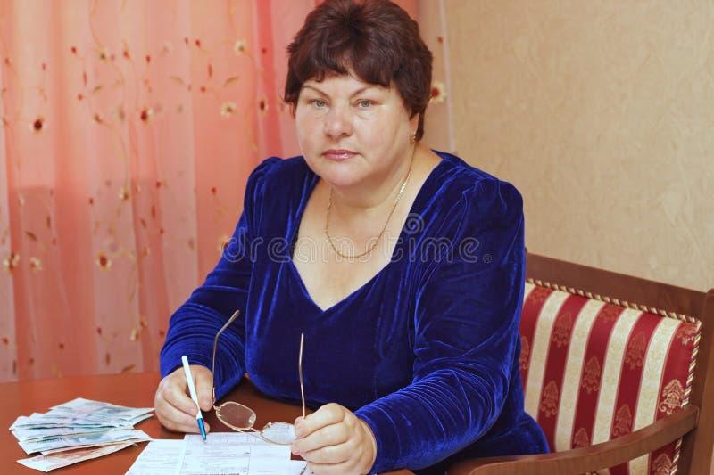 Uma mulher idosa enche recibos foto de stock royalty free