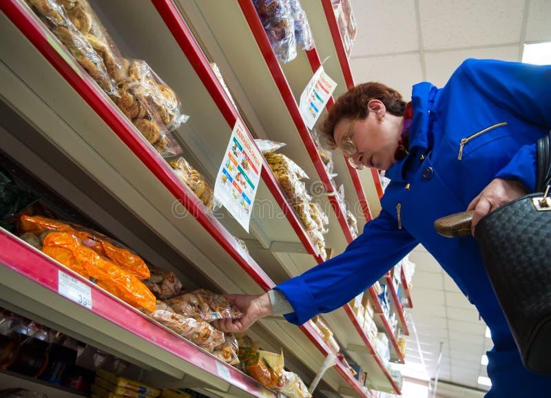 Uma mulher idosa escolhe doces nas prateleiras do ` do ímã do ` do supermercado foto de stock