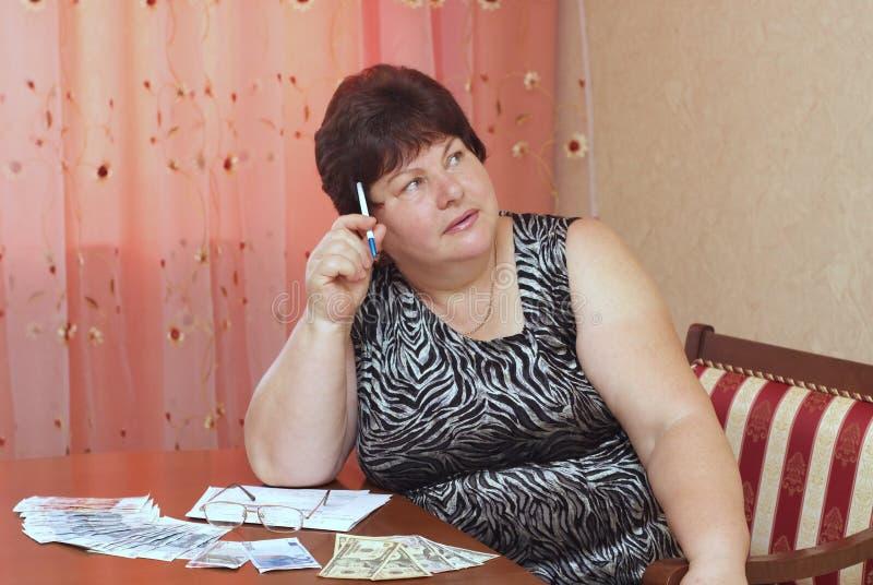 Uma mulher idosa está em uma tabela com dinheiro fotografia de stock royalty free