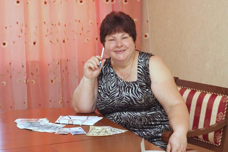 Uma mulher idosa está em uma tabela com dinheiro foto de stock