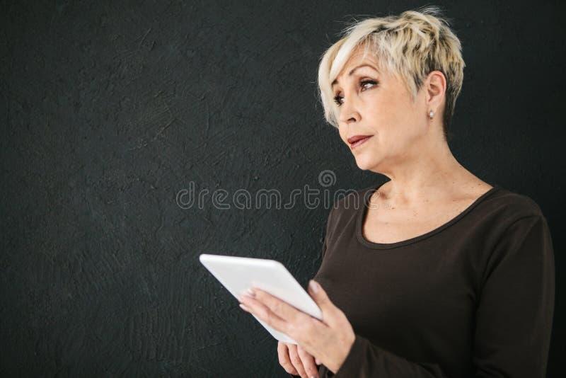 Uma mulher idosa moderna positiva bem sucedida guarda uma tabuleta em suas mãos e usa-a A geração mais velha e moderno fotografia de stock royalty free