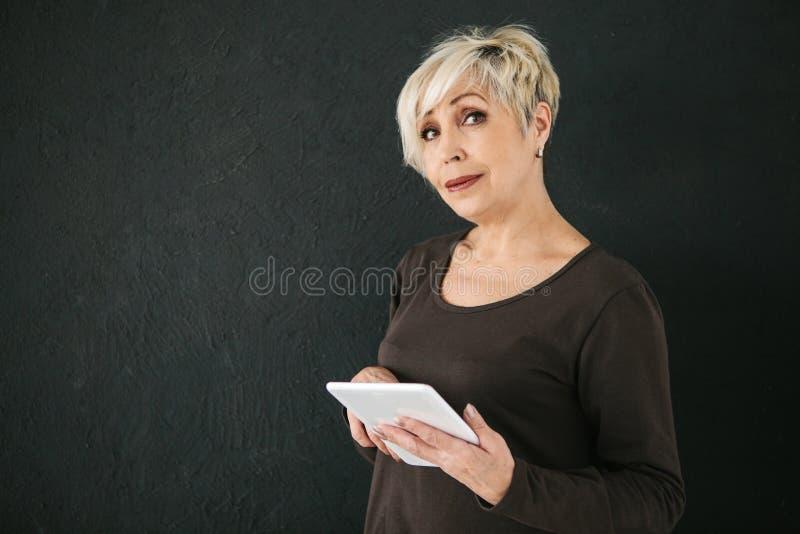 Uma mulher idosa moderna positiva bem sucedida guarda uma tabuleta em suas mãos e usa-a A geração mais velha e moderno imagens de stock