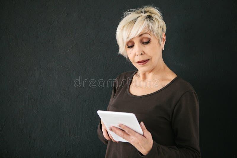 Uma mulher idosa moderna positiva bem sucedida guarda uma tabuleta em suas mãos e usa-a A geração mais velha e moderno imagem de stock royalty free
