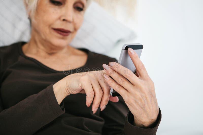 Uma mulher idosa moderna positiva está guardando um telefone celular e está usando-o A geração mais velha e a tecnologia moderna imagem de stock