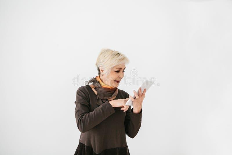 Uma mulher idosa moderna positiva guarda uma tabuleta em suas mãos e usa-a A geração mais velha e a tecnologia moderna fotografia de stock