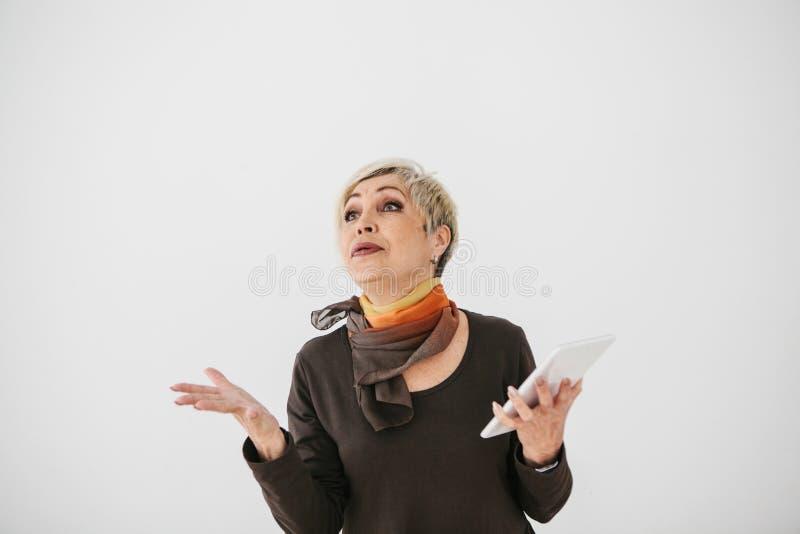 Uma mulher idosa moderna positiva guarda uma tabuleta em suas mãos e usa-a A geração mais velha e a tecnologia moderna imagens de stock