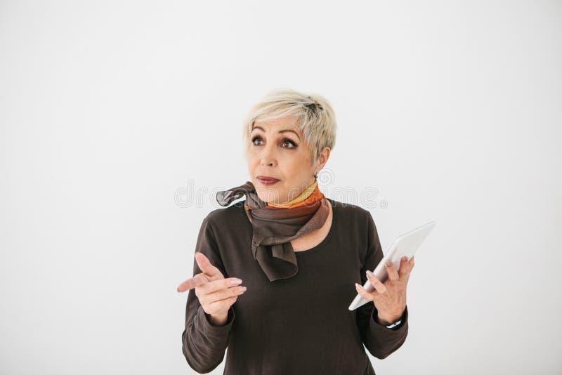 Uma mulher idosa moderna positiva guarda uma tabuleta em suas mãos e usa-a A geração mais velha e a tecnologia moderna foto de stock royalty free