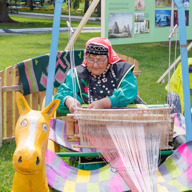 Uma mulher idosa na roupa Bashkir é assentada em um tear e tece um tapete Feriado nacional Sabantuy no parque da cidade fotografia de stock