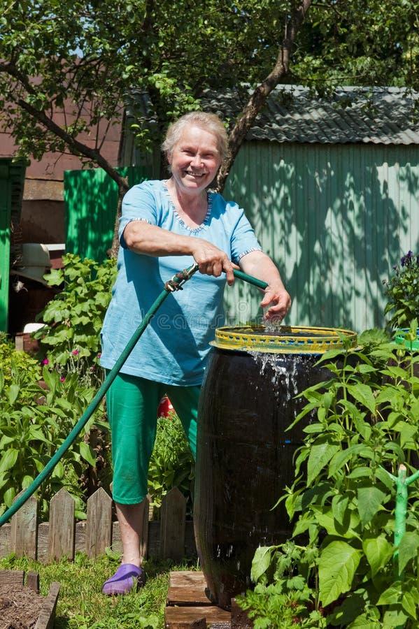 Uma mulher idosa no jardim com água fotografia de stock royalty free