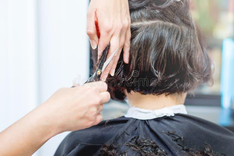 Uma mulher idosa no salão de beleza do cabeleireiro O feiticeiro faz os cabelos imagem de stock