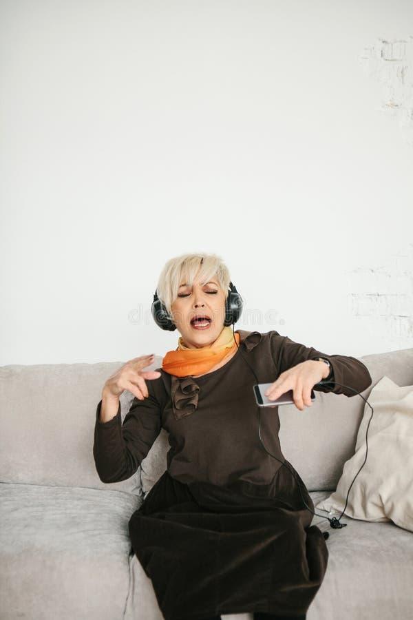 Uma mulher idosa positiva escuta a música e canta A geração e as novas tecnologias mais velhas foto de stock royalty free