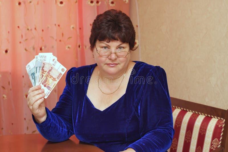 Uma mulher idosa prende o dinheiro em uma mão fotografia de stock