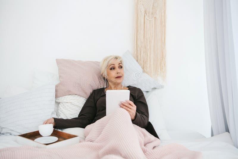 Uma mulher idosa que encontra-se no café bebendo da manhã da cama usa uma tabuleta para ver a notícia ou conversar com amigos em  fotografia de stock