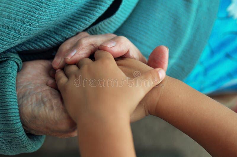 Uma mulher idosa que guarda as mãos do ` s das crianças, um bastão de madeira na rua bisavó e grande-neto imagem de stock royalty free